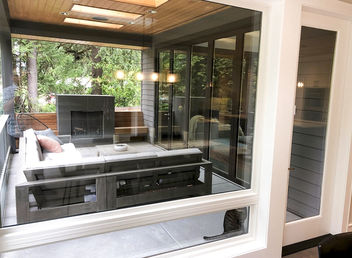 The outdoor living offers a fireplace, an L-shaped sofa, a round chair, and a wooden coffee table.
