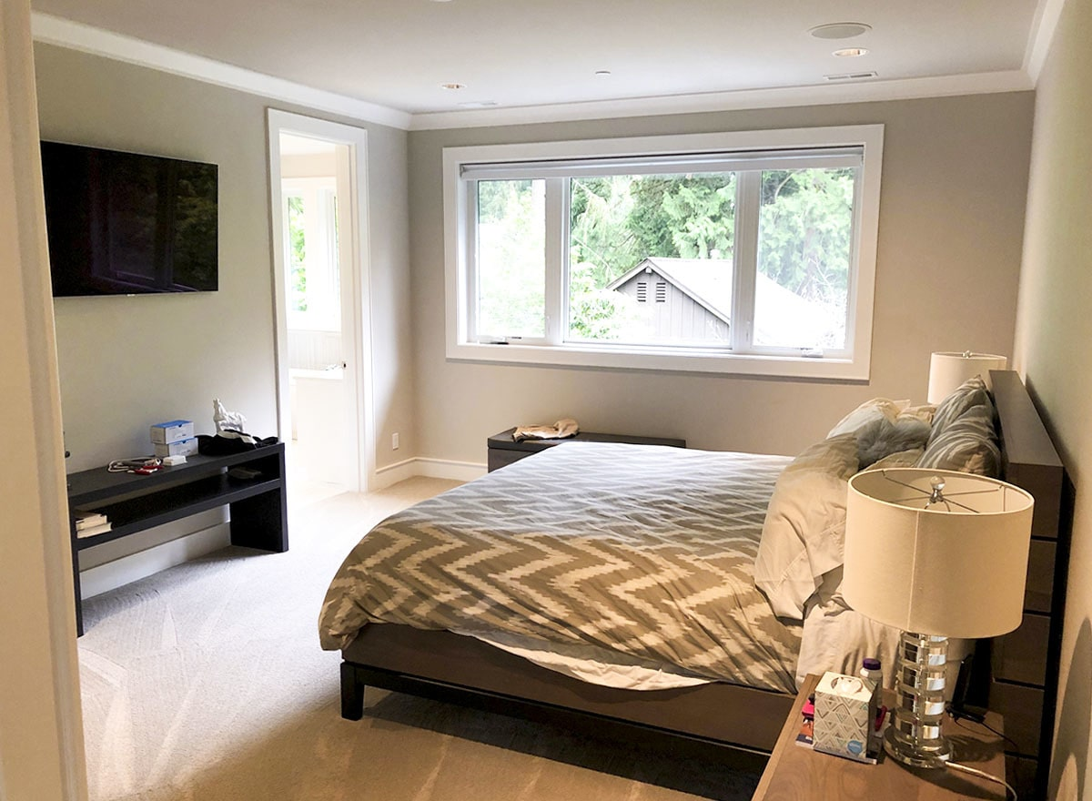 Primary bedroom with dark wood furnishings, white-framed windows, and a wall-mounted TV fixed above the black console table.