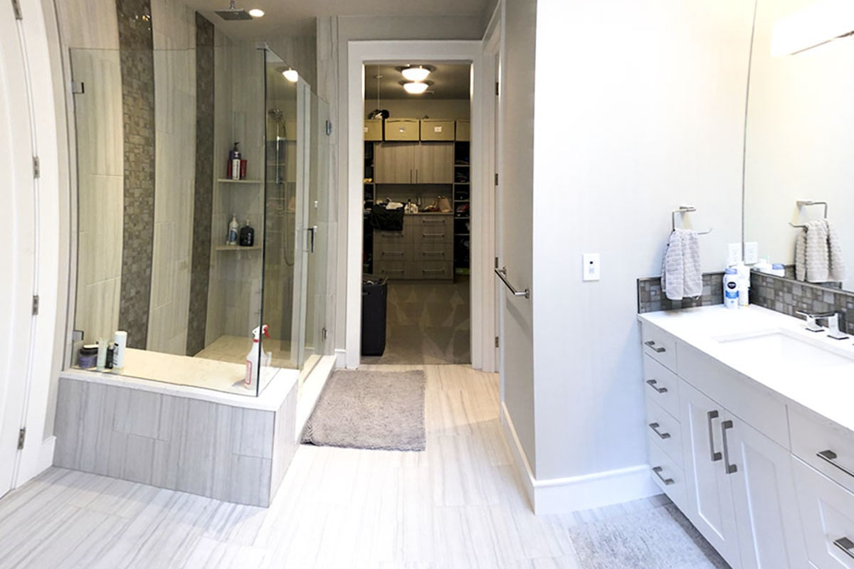 The primary bathroom is equipped with white sink vanity and a walk-in shower with corner shelves and a tile bench.