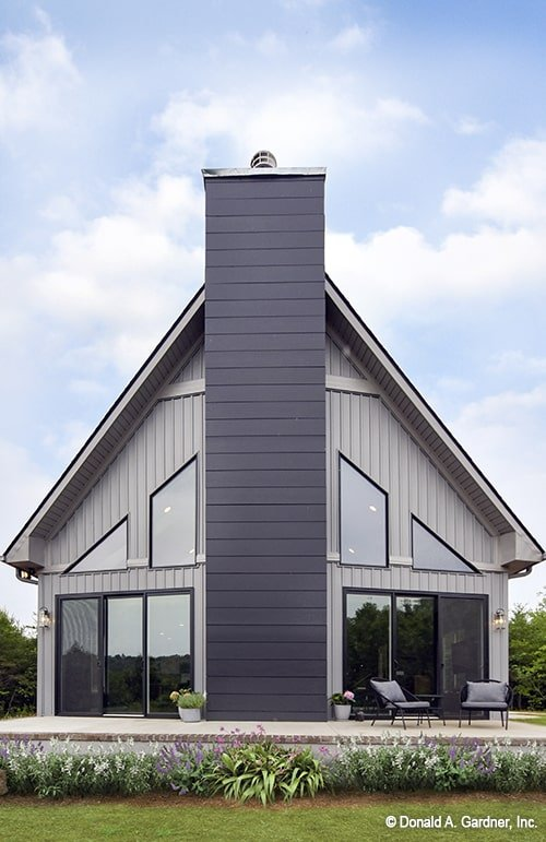 Front exterior view showing the vertical siding, tall windows, a chimney, and a spacious deck.