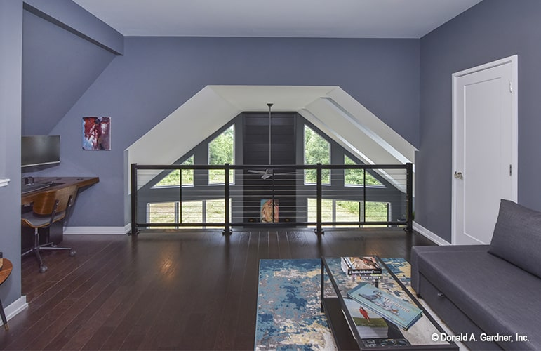 An open loft with a built-in desk, gray sofa, and a glass top coffee table sitting on a printed area rug.