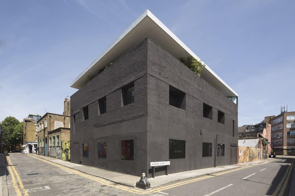 This is a view of the house from the street. You can see here the matte black exterior walls with different textures for the ground floor and the upper floor contrasted by the bright roof.