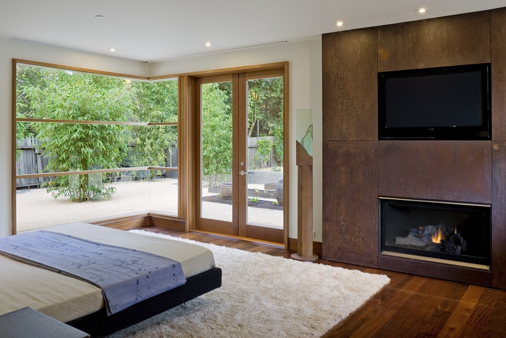 The bedroom has a large glass wall and a set of glass doors that bring in natural lighting for the platform bed and the dark wall across from it that houses the fireplace and TV.