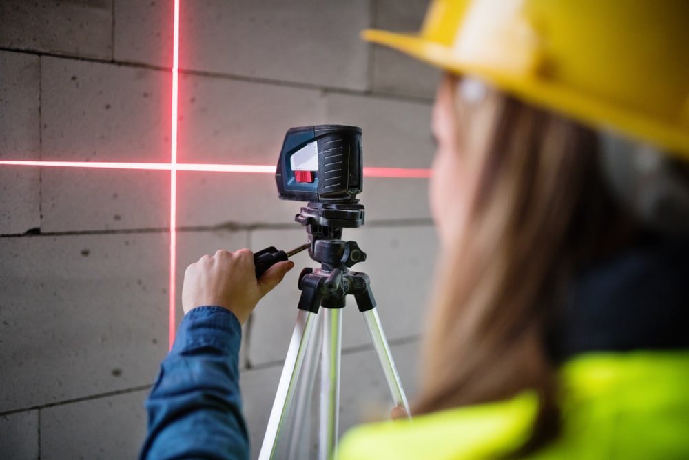 A construction worker using a laser equipment in a building site.