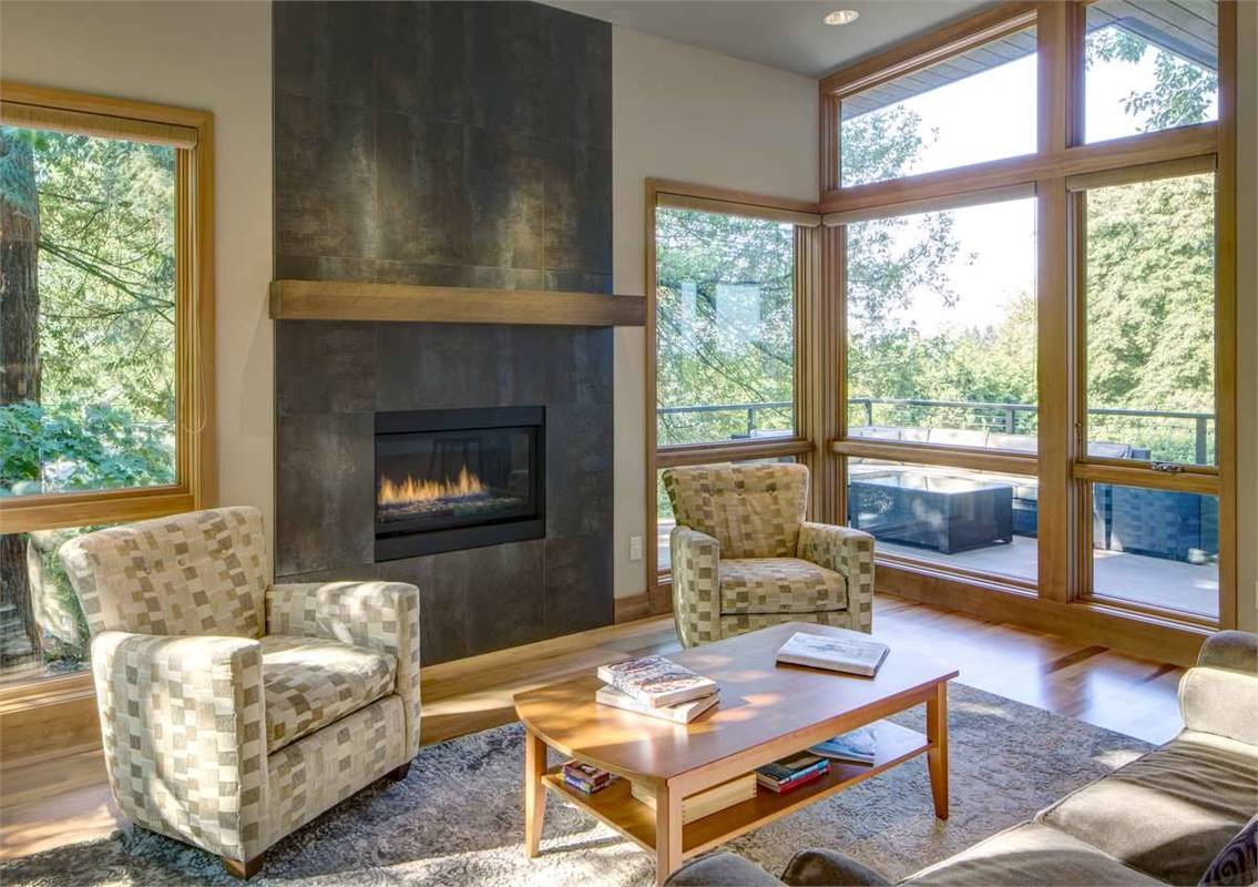 The living room has a gray sofa, wooden coffee table, printed armchairs, and a glass-enclosed fireplace.