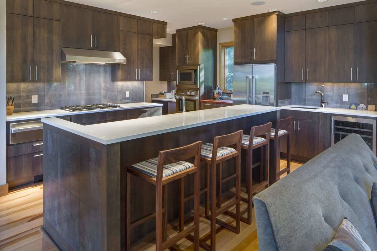 The kitchen is equipped with quartz countertops, dark wood cabinetry, stainless steel appliances, and a breakfast island.