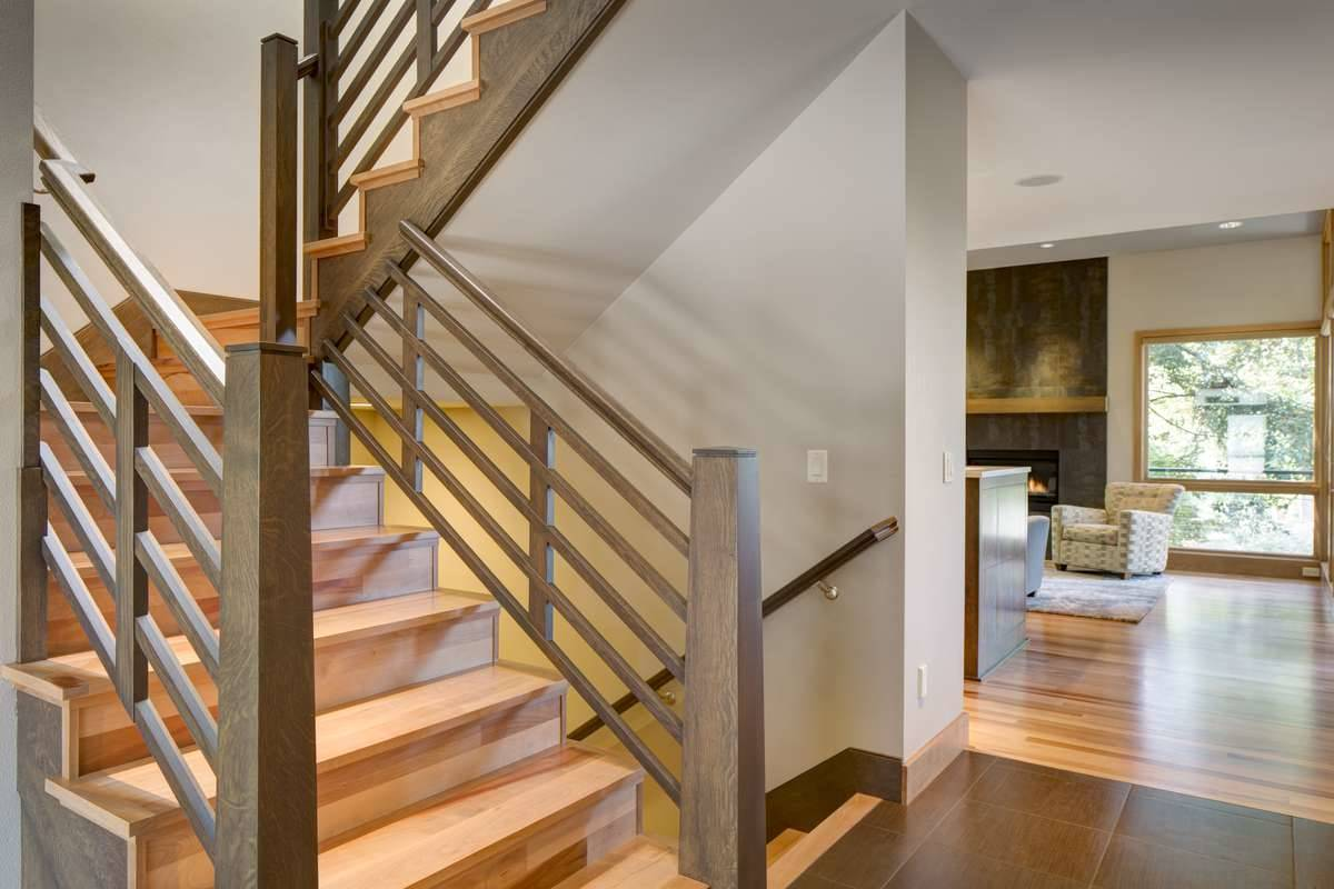 A wooden staircase in the foyer leads to the sleeping quarters upstairs and the media room downstairs.