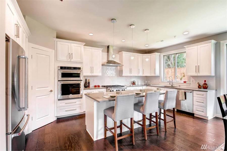 Kitchen with white cabinetry, stainless steel appliances, granite countertops, and a breakfast island bar.