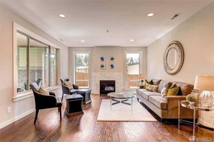 The living room offers a sectional sofa, gray armchairs, round glass top tables, and a fireplace flanked by tall windows.