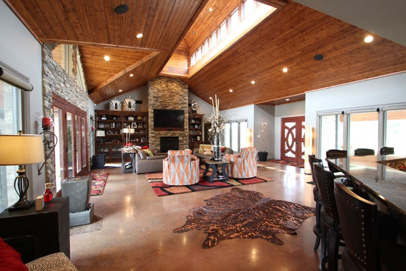 View of the living room from the kitchen showing a wooden vaulted ceiling and polished concrete flooring topped by cowhide and multi-colored rugs.