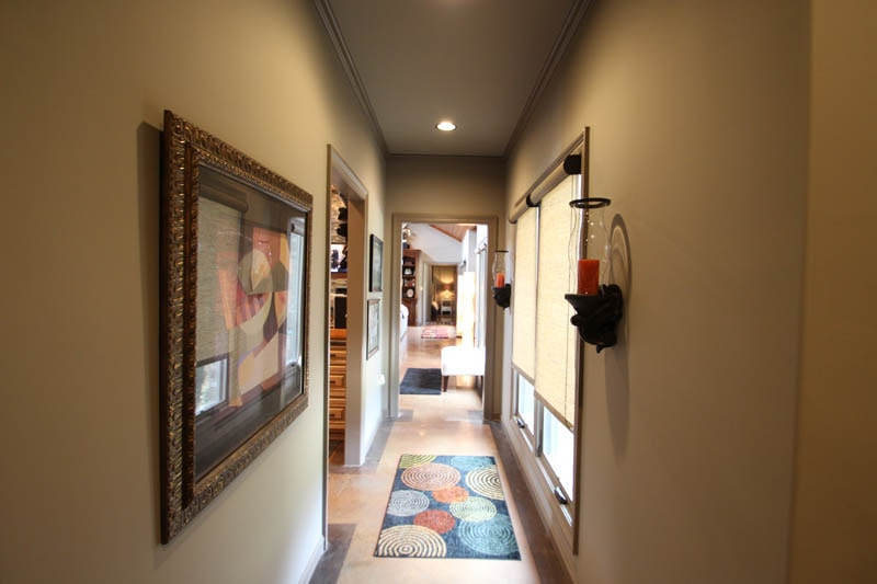 This hallway is adorned with a colorful rug, candle sconces, and interesting framed artworks.