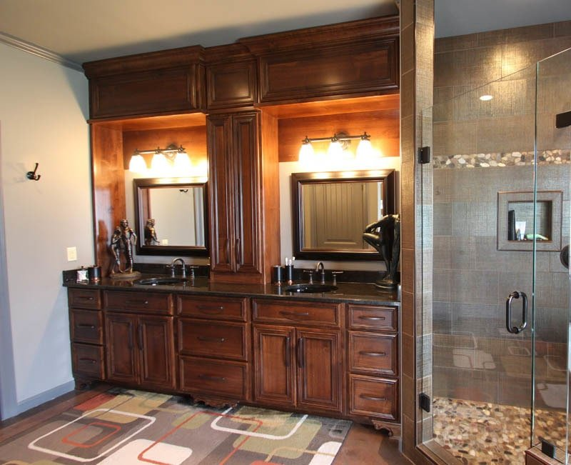 A large patterned rug complements the dark wood vanity with dual sink and copper fixtures.