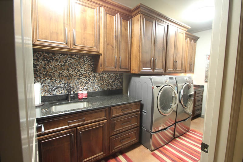 The utility room is filled with wooden modular cabinets, front load appliances, and an undermount sink fitted on the granite countertop.