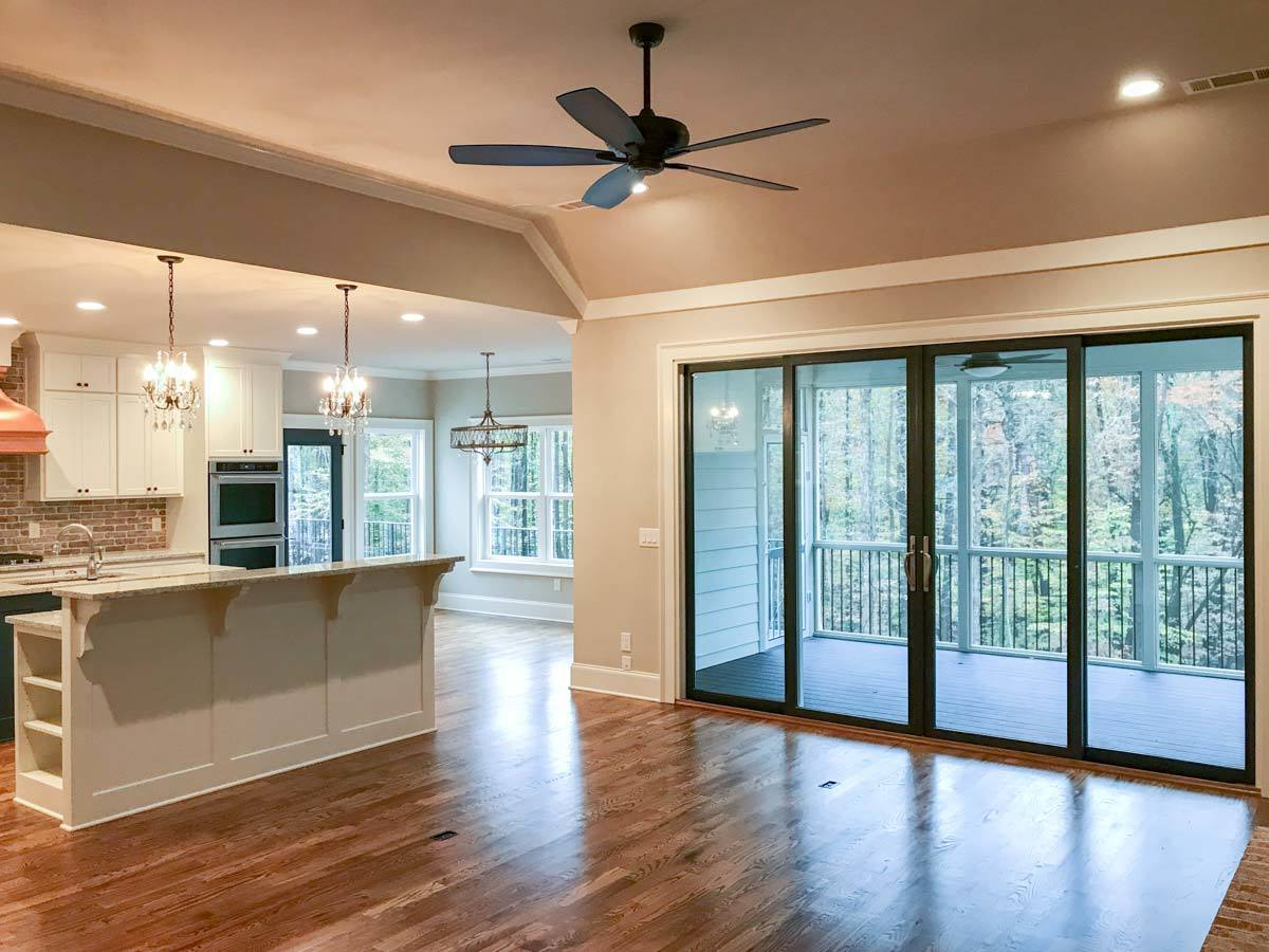 The living area has a coved ceiling and glass double door that opens to the screened porch.