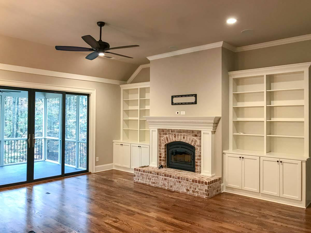 White built-in cabinets flank the brick fireplace that's enclosed in an arched glass panel.