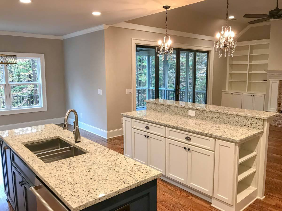 The two kitchen islands have granite countertops and built-in cabinets.