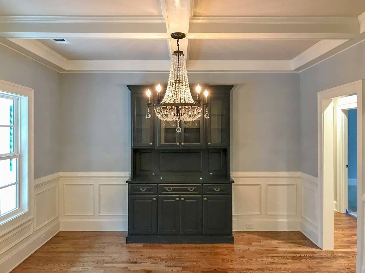 Formal dining room with a beaded chandelier, black display cabinet, and gray walls adorned with white wainscoting.