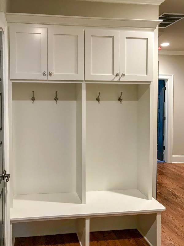 The mudroom has built-in storage with white cabinets, coat hooks, and a multi-purpose bench.