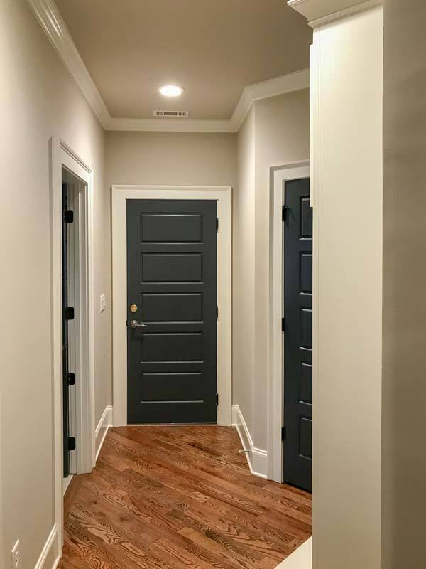 This hallway leads to the bedrooms enclosed in black wooden doors.