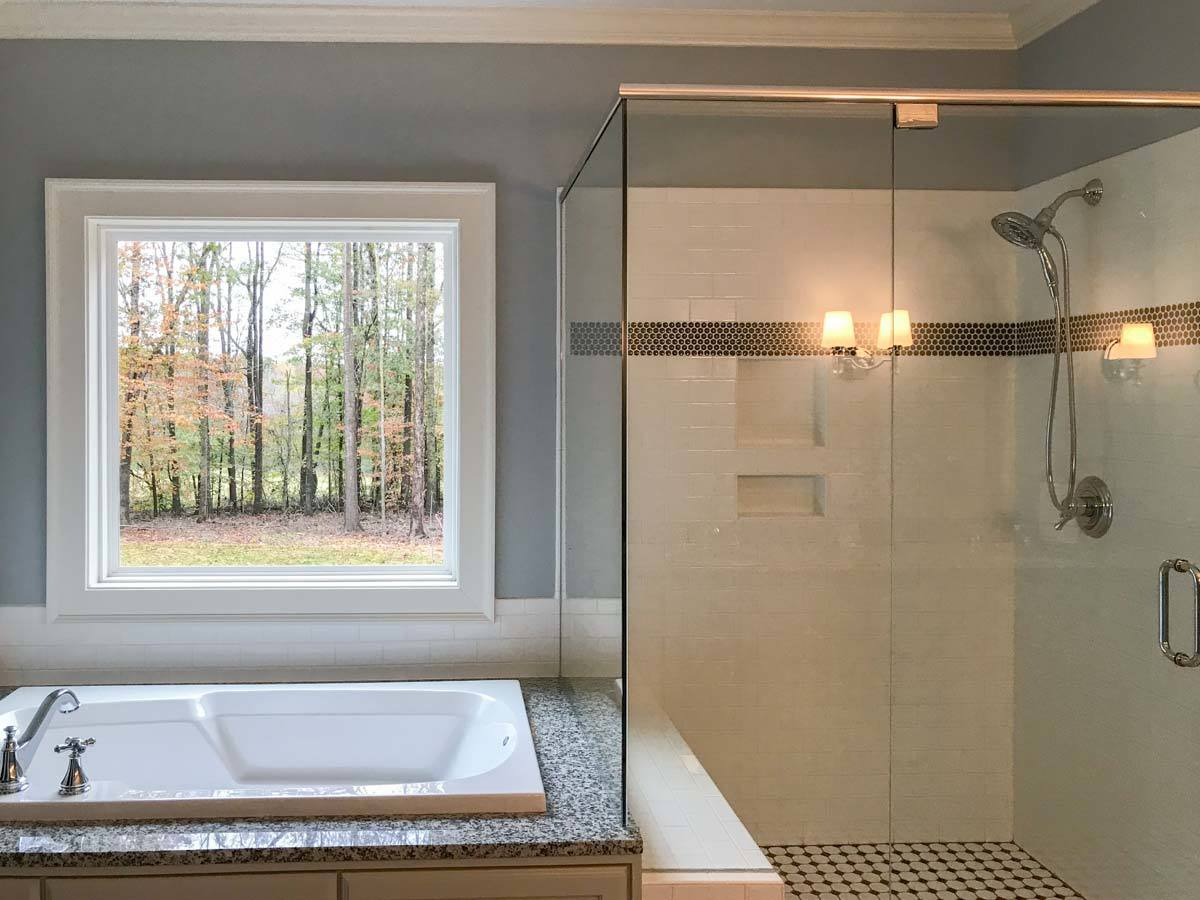 The primary bathroom has a walk-in shower and a drop-in bathtub placed under the picture window.