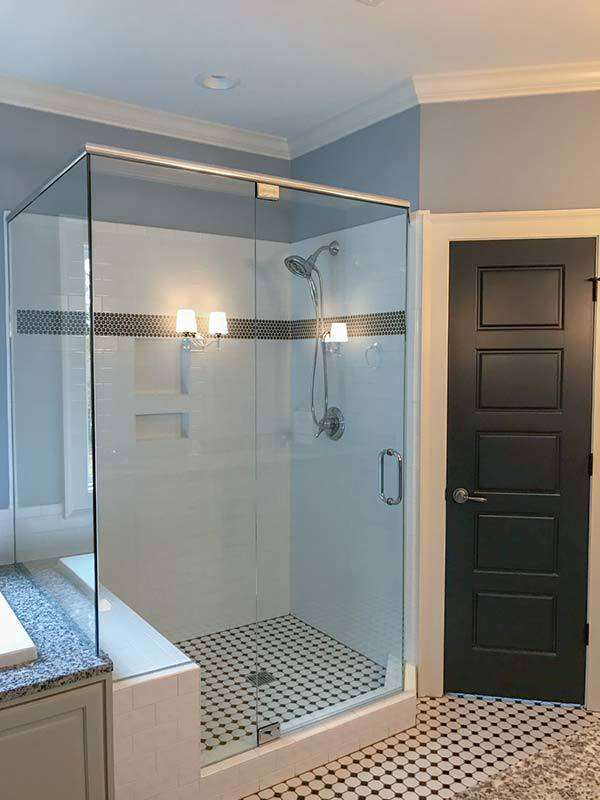The walk-in shower has white subway tile walls, inset shelves, and chrome fixtures.