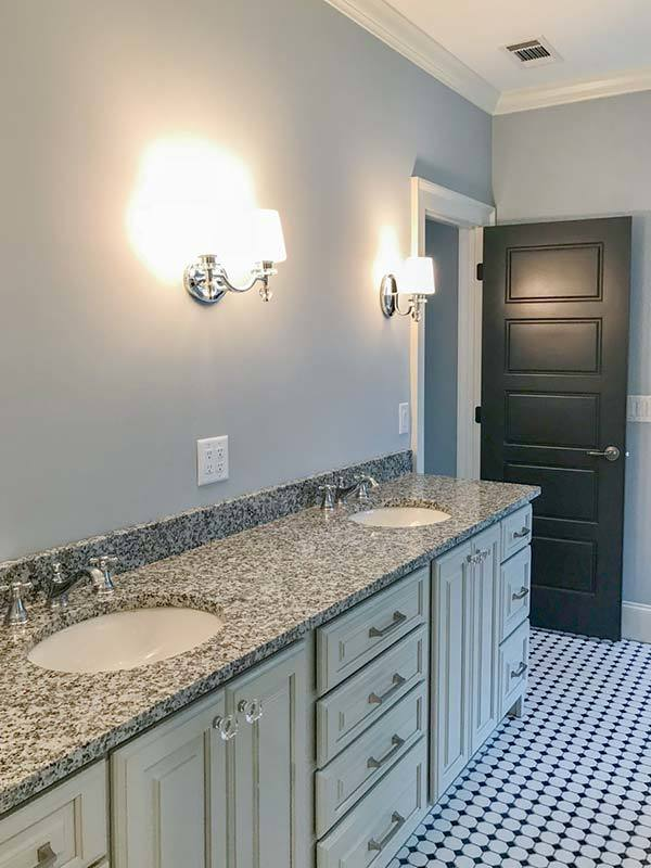Dual sink vanity lit by glass sconces complete the primary bathroom.