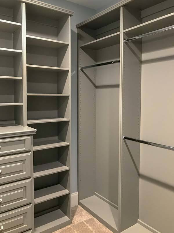 The walk-in closet is filled with gray shelvings, drawers, and built-in pole racks.
