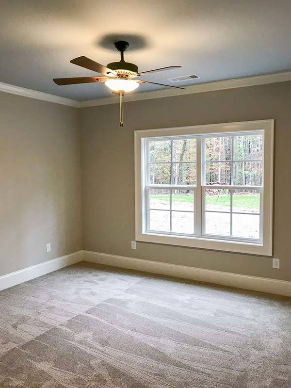 This bedroom has carpet flooring, beige walls, a traditional ceiling fan, and a white framed window that invites natural light in.