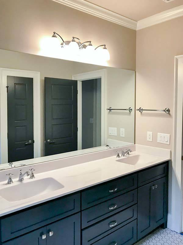 This bathroom features a dual sink vanity paired with a large frameless mirror.
