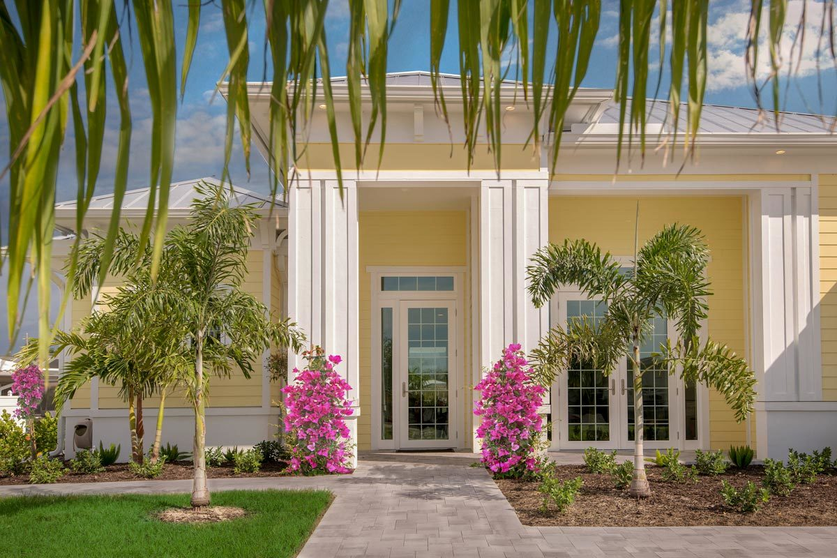 Home entry featuring a glass front door and decorative columns accentuated with colorful flowers.