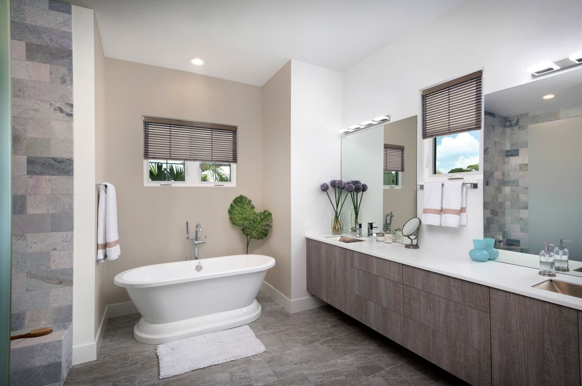 The primary bathroom offers a freestanding tub and a dual sink vanity paired with frameless mirrors.