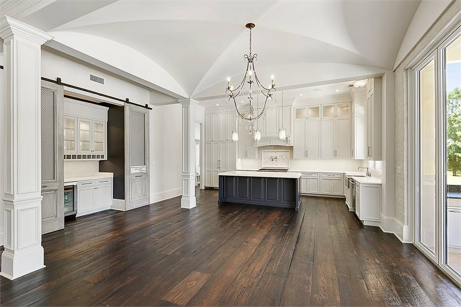 Spacious kitchen with wide plank flooring, white cabinets, and a groin vault ceiling mounted with glass pendants and an ornate chandelier.