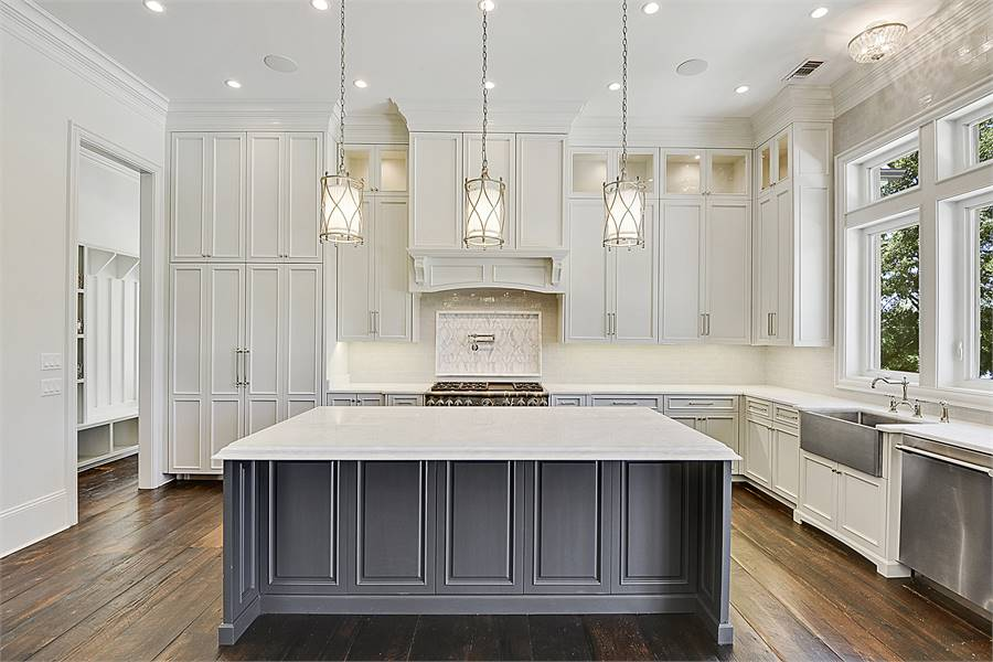 The kitchen is equipped with marble countertops, stainless steel appliances, a farmhouse sink, and a center island bar.