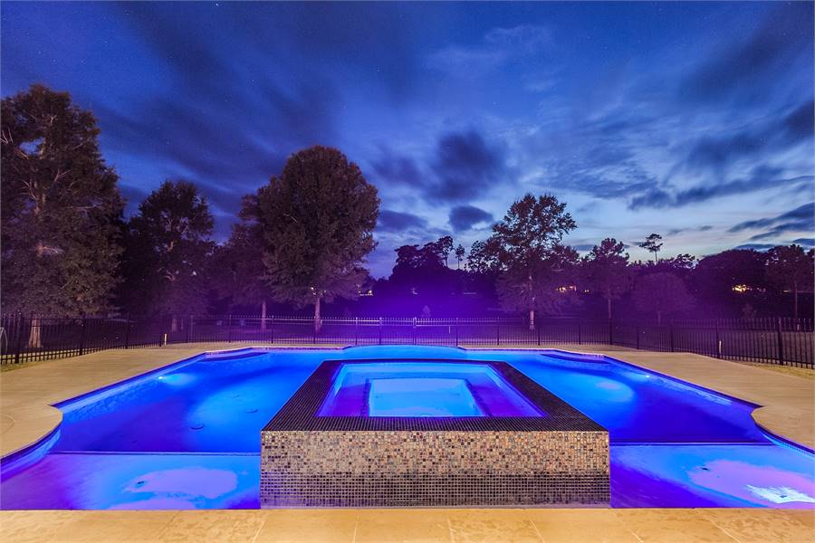 The built-in spa clad in black mosaic tiles is placed in the middle of the pool.