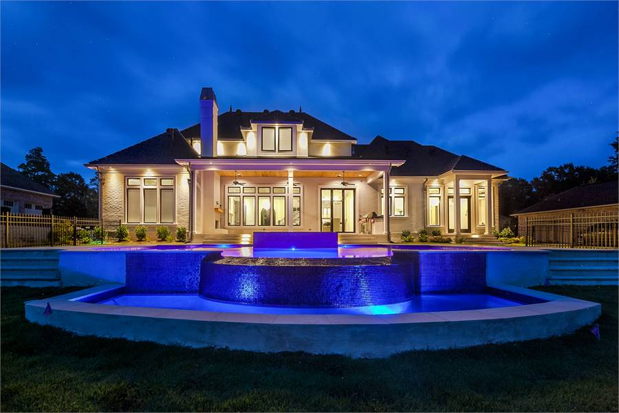 View of the house from the backyard boasting its spacious porch and pool deck.