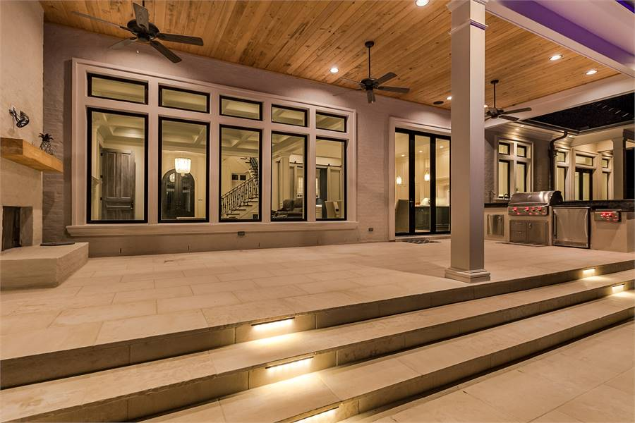 Back porch with a summer kitchen, fireplace, and sleek fans hanging from the wood-paneled ceiling.