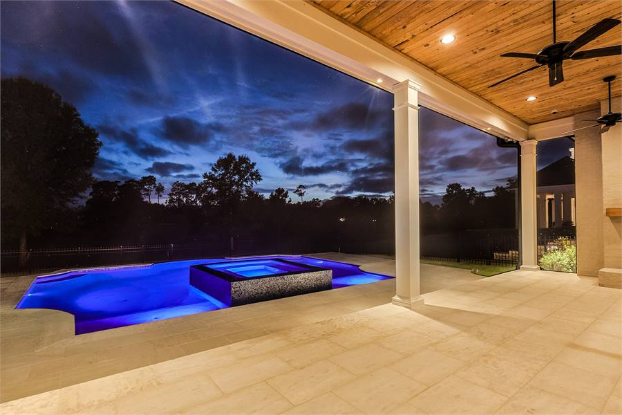 There's a swimming pool and an integrated spa across that stand out against the dark sky.