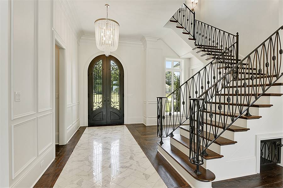 The foyer has an arched front door, a beaded chandelier, and marble herringbone tile flooring that transitions to the dark hardwood floor.