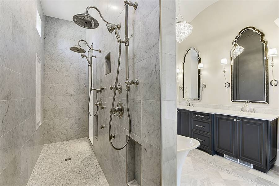 The shower area features two shower heads, chrome fixtures, and inset shelves.