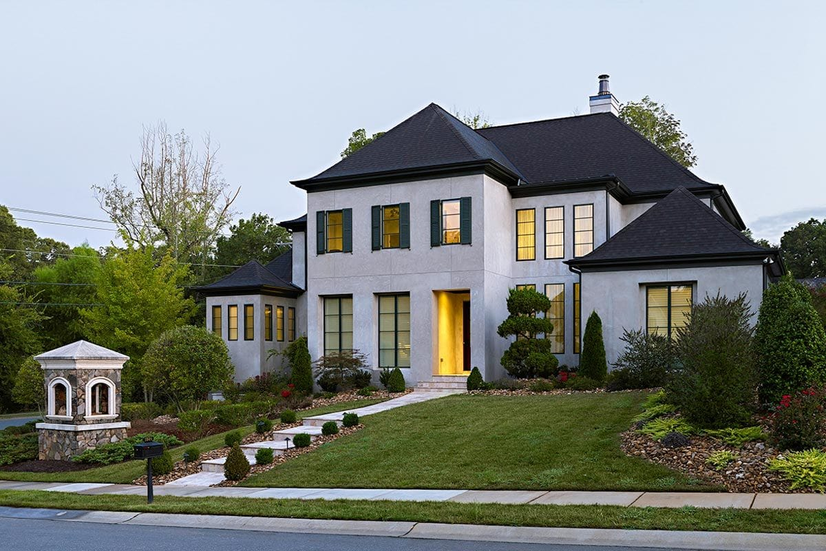 Angled front view showing the verdant landscaping and a sloping walkway leading to the home entry.