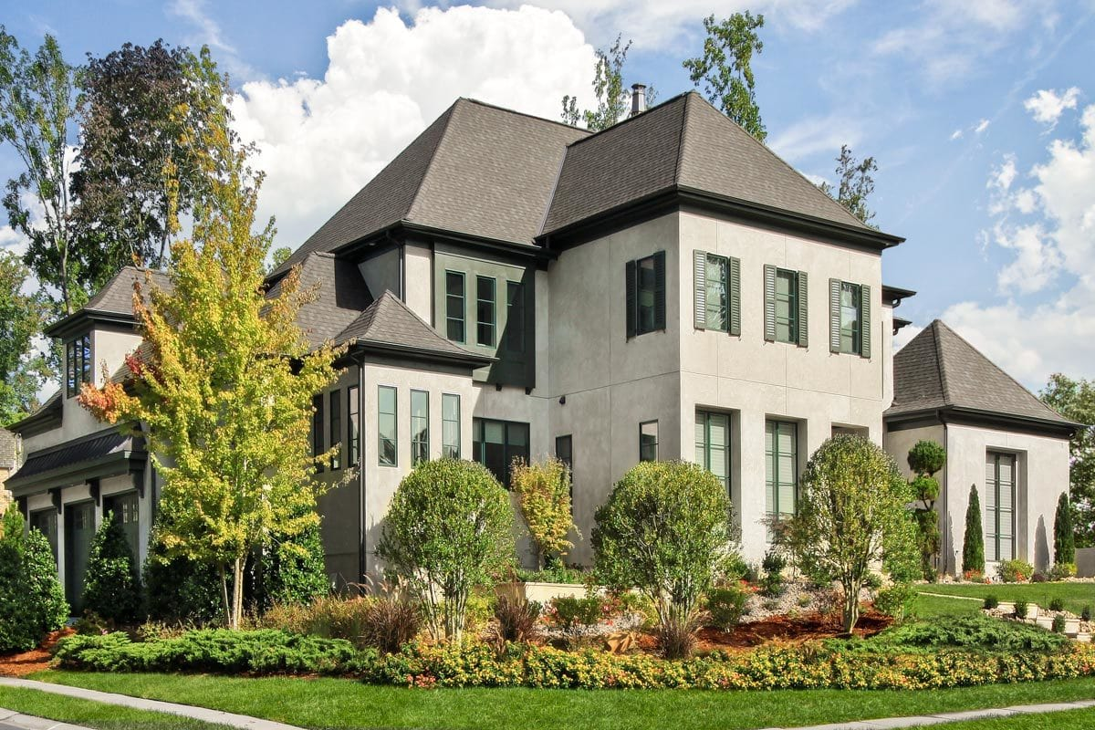 Well-manicured plants and lush green lawn complement the modern house.