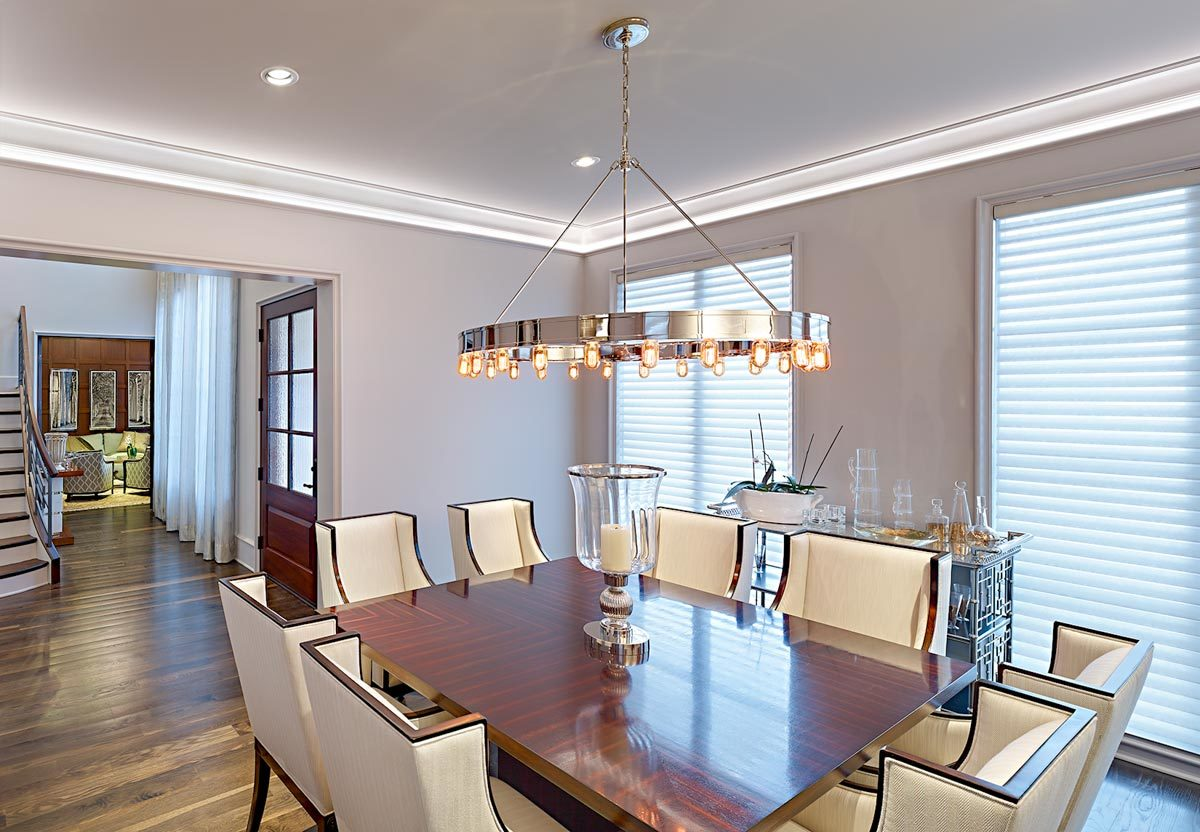 The dining area has an ornate buffet bar, a dining table for eight, and a round chandelier.