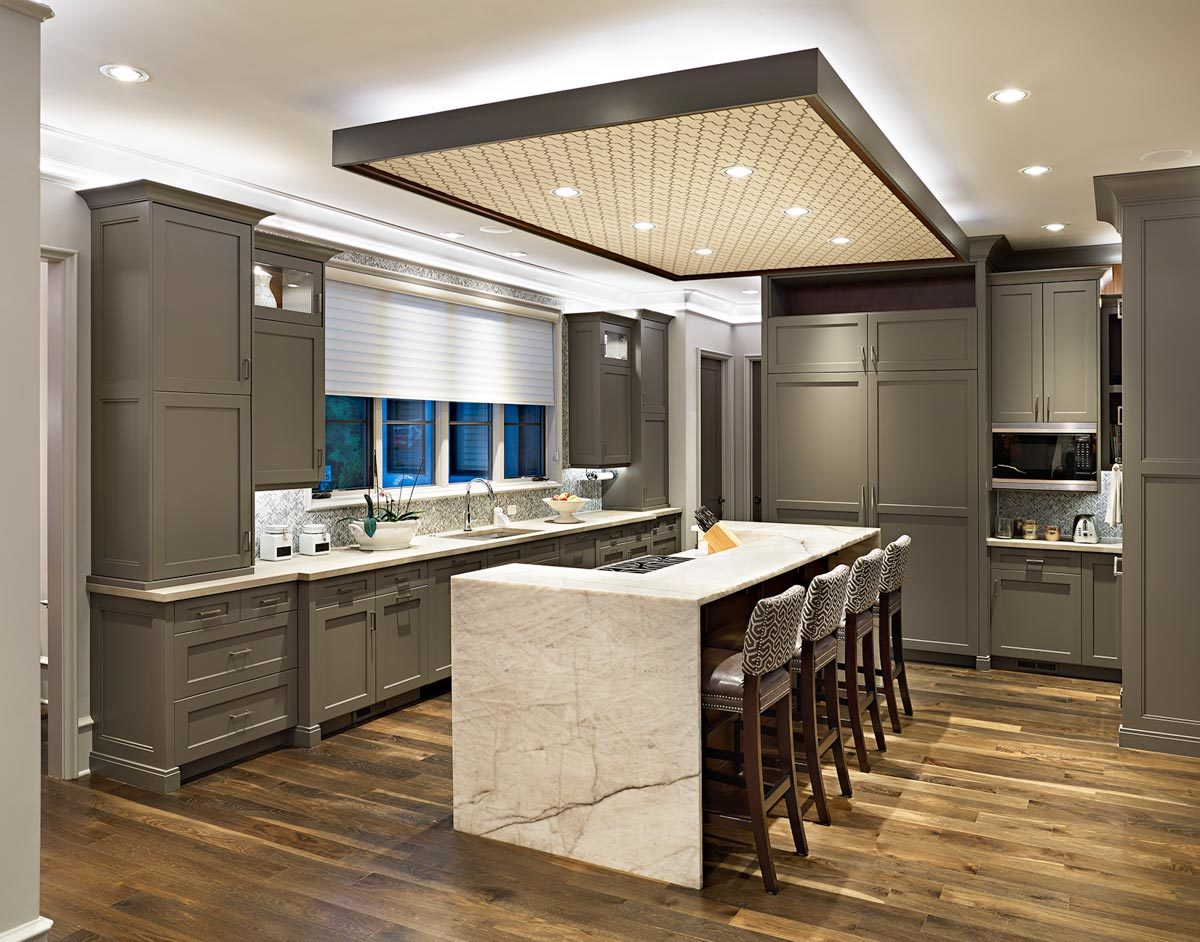 The kitchen is equipped with marble countertops, gray cabinetry, and a two-tier island lined with leather stools.