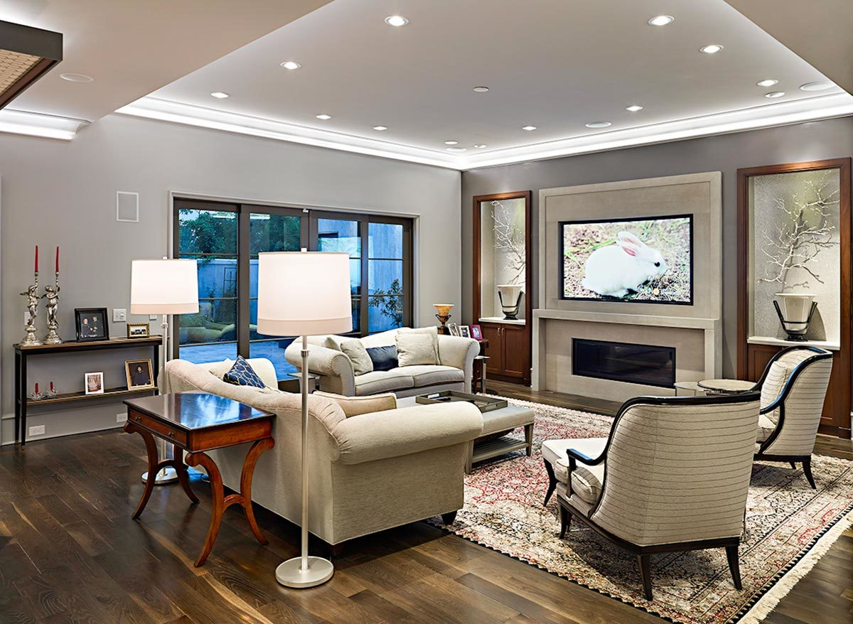 Glass-enclosed fireplace, wall-mounted TV, and inset cabinets complete the living room.