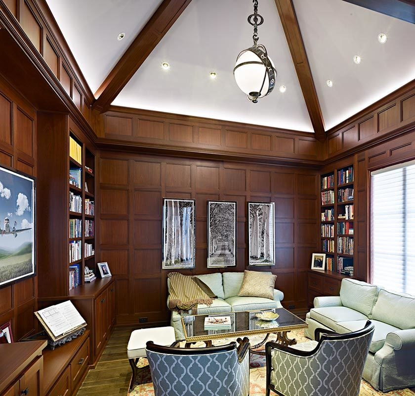 Library with hardwood flooring, wood-paneled walls, and a beamed ceiling fitted with a glass globe chandelier and recessed lights.