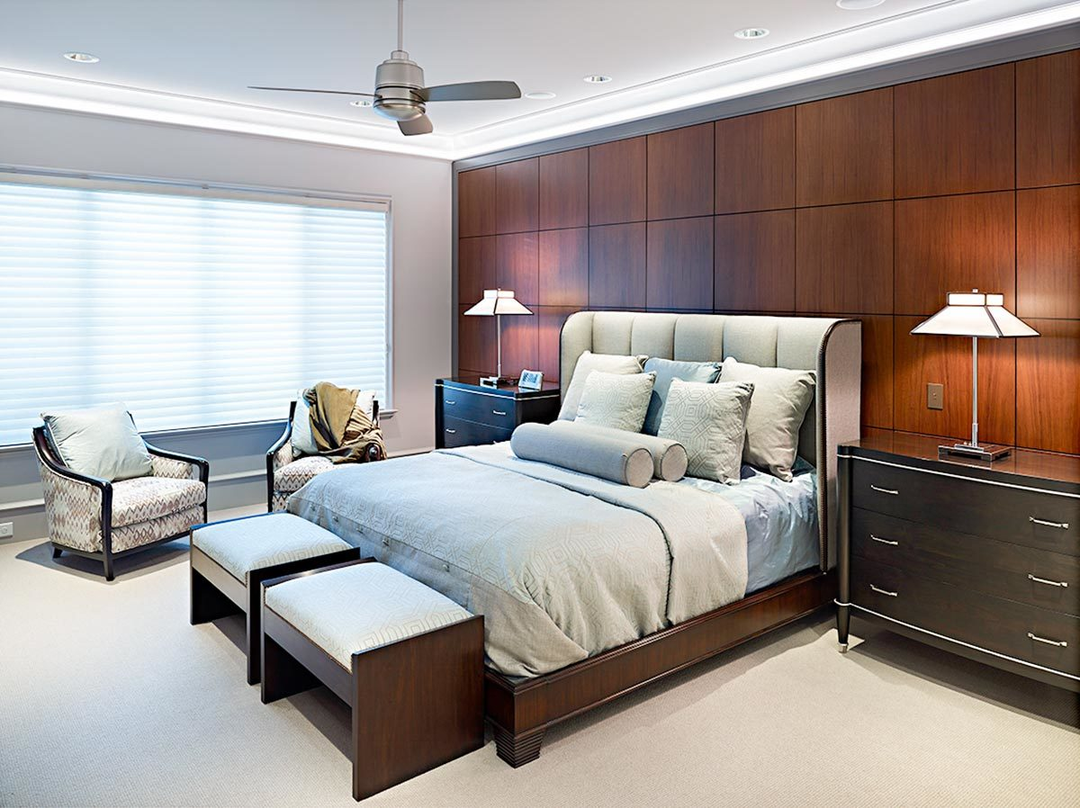 The primary bedroom has cushioned seats, matching nightstands, and a wingback bed with a pair of footstools at its end.