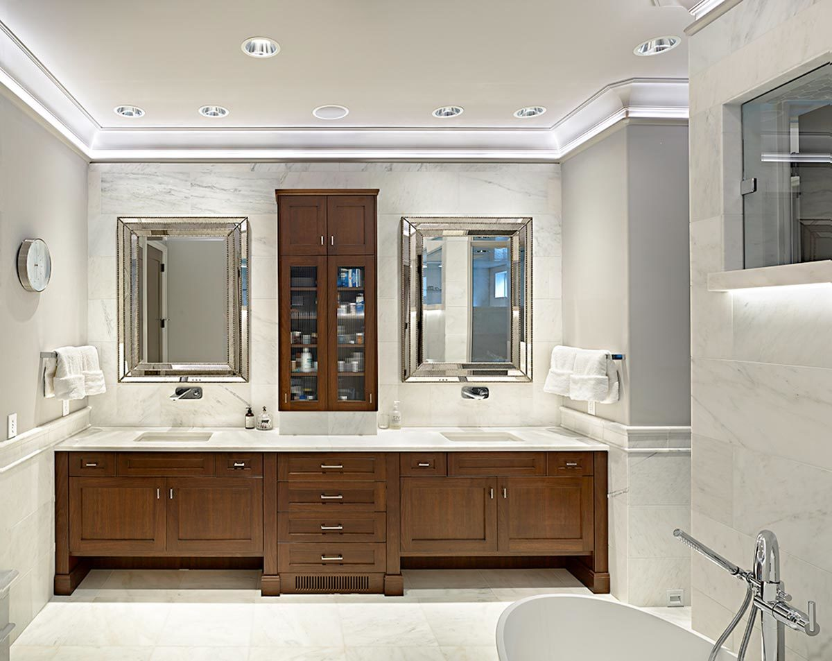 The primary bathroom offers a freestanding tub and a dual sink vanity paired with chrome framed mirrors.