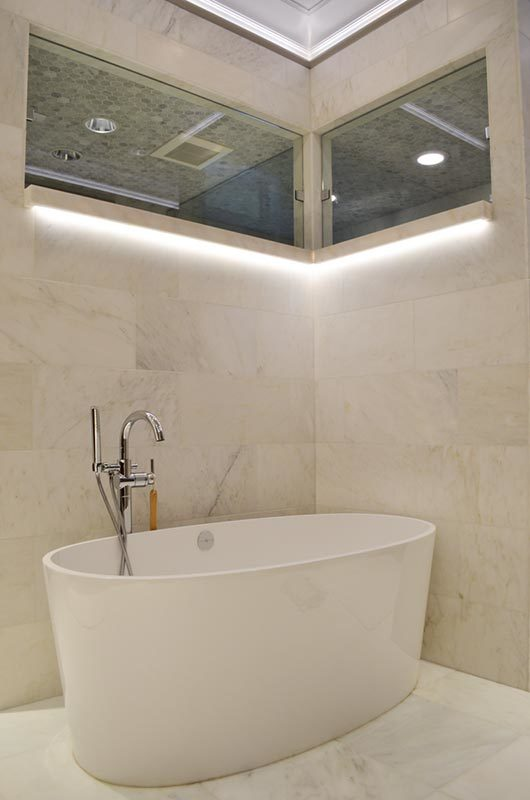 The freestanding tub blends in with the white marble tiled flooring and walls.