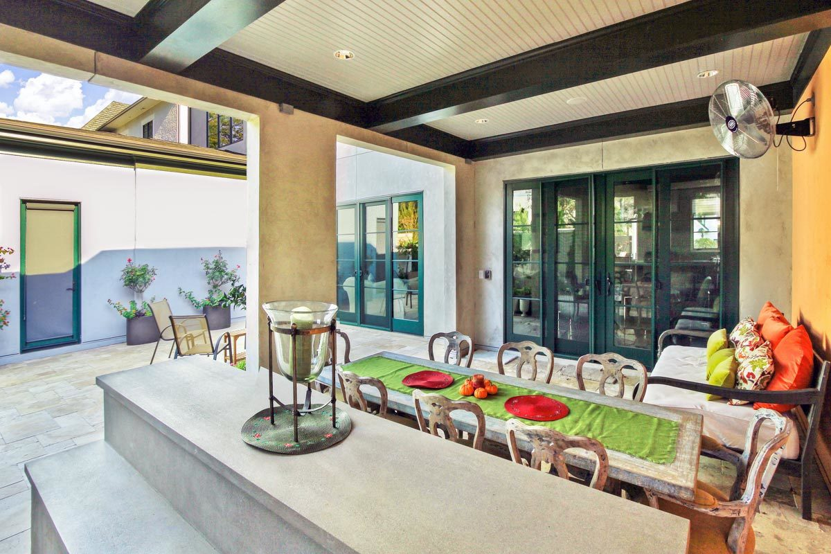 Veranda with a rustic dining set and a cushioned sofa filled with bright multi-colored pillows.
