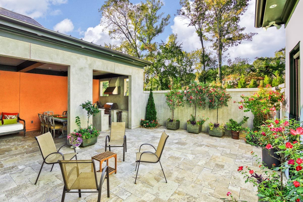 A farther view shows the summer kitchen and outdoor chairs surrounding a small, wooden table.